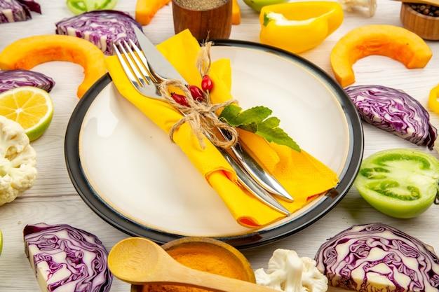 Vista dal basso legato forchetta e coltello sul tovagliolo giallo sul piatto bianco tagliare le verdure cavolo rosso zucca cavolfiore peperone giallo sul tavolo di legno bianco
