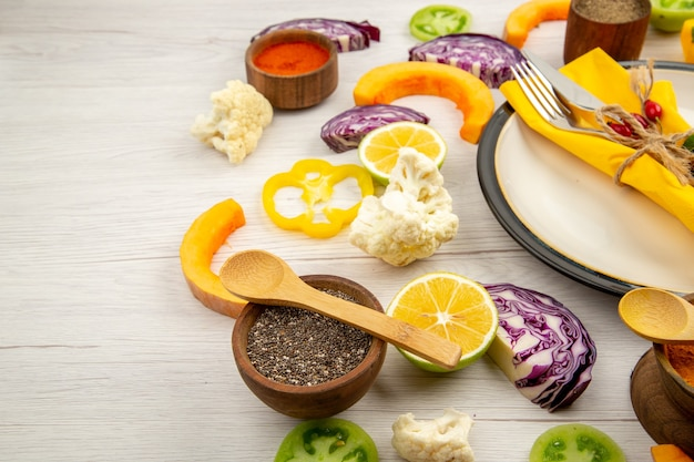 Vista dal basso legato coltello e forchetta con tovagliolo giallo sul piatto bianco verdure tagliate cavolo rosso zucca cavolfiore peperone giallo spezie in piccole ciotole sul tavolo di legno bianco
