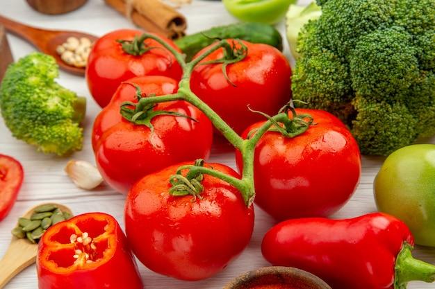 Вид снизу томатная ветка брокколи деревянные ложки чеснока на сером столе