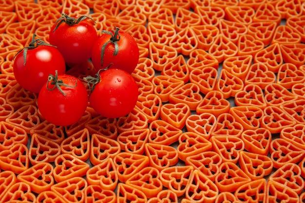 Bottom view tometoes on heart shaped italian pasta on dark surface
