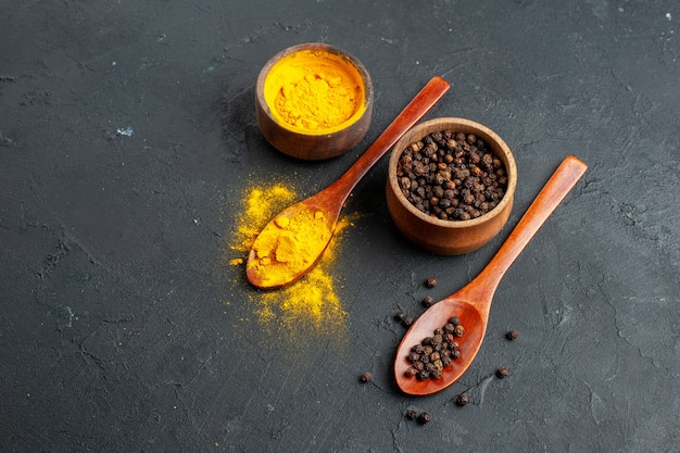 Bottom view turmeric black pepper in small bowls in wooden spoons on black surface