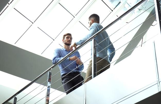 底面図。ビジネス会議中にオフィスで話し合うカジュアルウェアの2人のビジネスマン