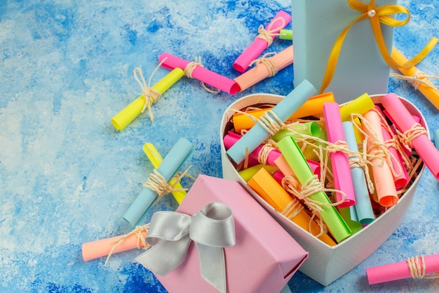 Вид снизу день святого валентина концепция свиток пожелания бумаги в коробке в форме сердца подарки на синем фоне