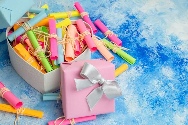 Вид снизу день святого валентина концепция свиток желаемые бумаги в коробке в форме сердца праздничные подарки на синем фоне свободное пространство