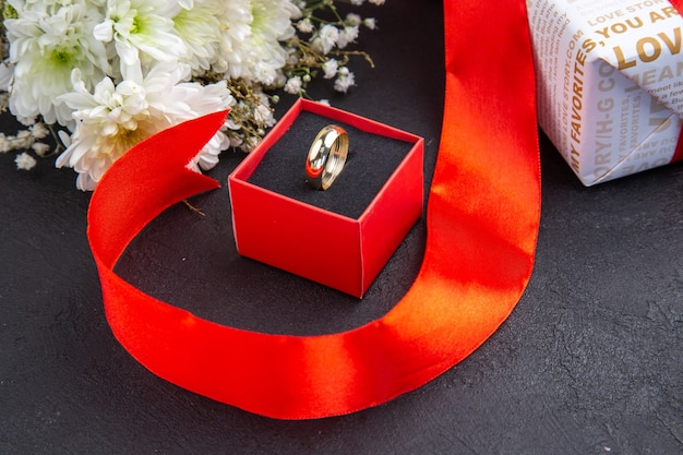 暗い背景のボックスの白い花の底面図バレンタインデーギフトリング