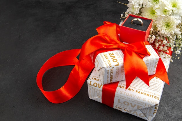 Вид снизу подарки на день святого валентина с красными лентами цветы кольцо в коробке на темном фоне