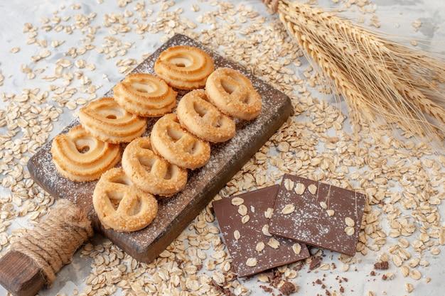 底面図まな板チョコレートのさまざまなビスケット小麦のスパイクテーブルに散らばったオーツ麦