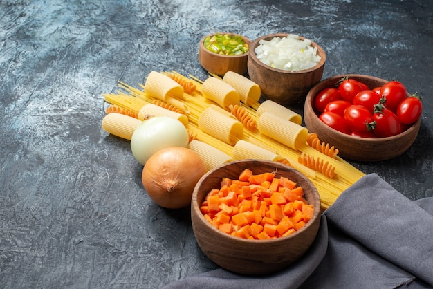 Вид снизу различные макароны ригатони спагетти спирали нарезанные овощи в мисках вкусные макароны на сковороде на сером фоне