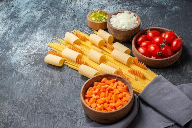 Вид снизу различные пасты ригатони спагетти спирали нарезанные овощи в деревянных мисках на сером фоне