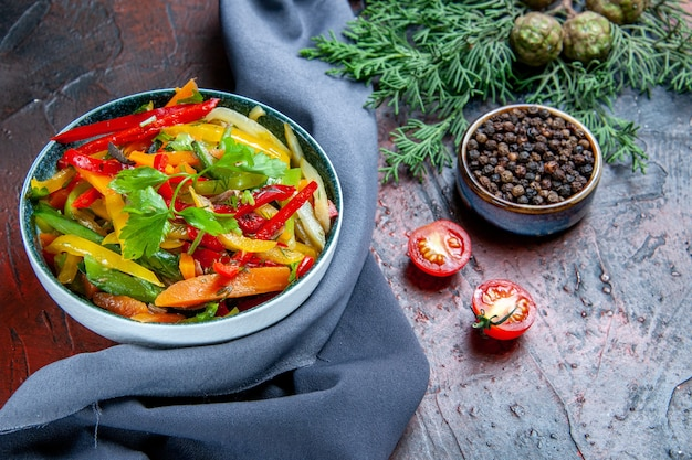 Insalata di verdure vista dal basso in una ciotola pepe nero in una piccola ciotola scialle blu oltremare del ramo di abete sul tavolo rosso scuro