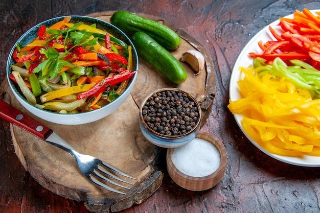 Insalata di verdure vista dal basso in una ciotola cetrioli forchetta pepe nero su tavola rustica peperoni tagliati sale su tavolo rosso scuro