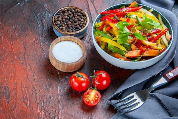 Insalata di verdure vista dal basso in ciotola blu oltremare scialle pomodorini spezie forchetta sul tavolo rosso scuro