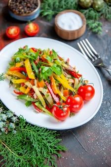 Insalata di verdure vista dal basso su piastra ovale pomodorini forchetta su superficie rosso scuro