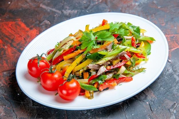 Insalata di verdure vista dal basso su piatto ovale su superficie scura