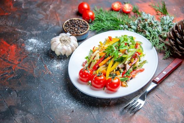 Insalata di verdure vista dal basso su piastra ovale forchetta aglio pepe nero su superficie rosso scuro