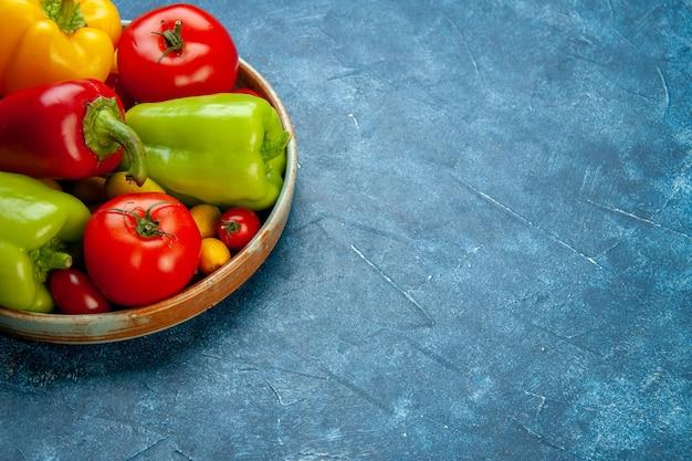하단보기 야채 체리 토마토 다른 색상 피망 파란색 표면 무료 장소에 나무 접시에 토마토