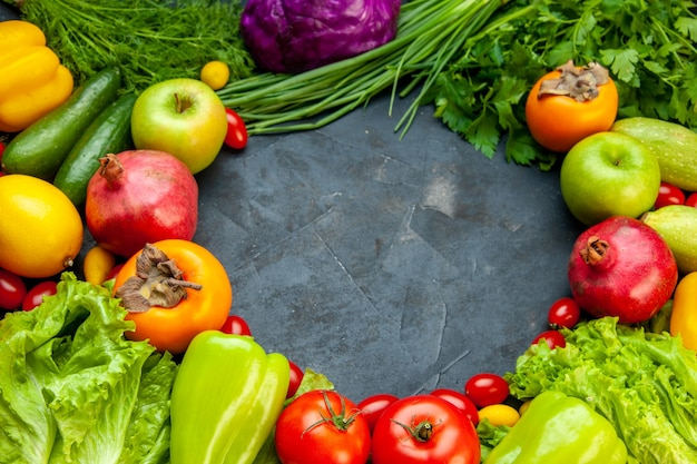 Vista dal basso frutta e verdura pomodorini cavolo rosso cipolla verde prezzemolo lattuga aneto peperoni verdi melograno cachi mela con spazio di copia