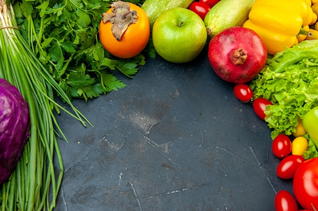 Vista dal basso frutta e verdura pomodorini cavolo rosso cipolla verde prezzemolo lattuga zucchine peperone giallo melograno cachi mela con spazio di copia