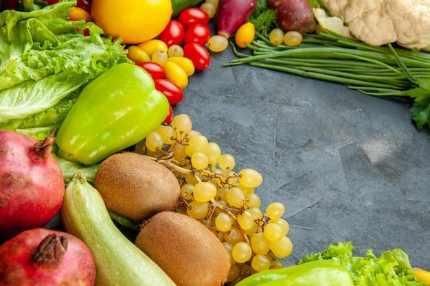 Vista dal basso frutta e verdura lattuga zucchine peperoni uva cipolla verde mela cotogna kiwi melograno spazio libero