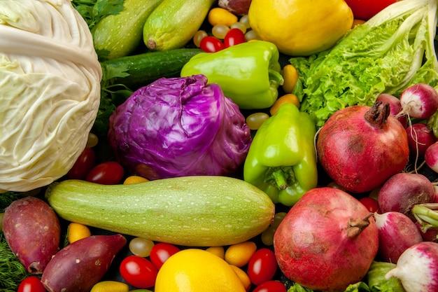 Vista dal basso verdura e frutta zucchine peperoni pomodorini cumcuat cetriolo lattuga cavolo rosso e bianco melograni ravanello