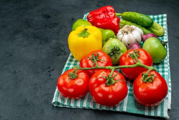 Vista dal basso verdure aglio cetrioli ramo di pomodoro pomodori verdi peperoni sulla tovaglia verde sul tavolo nero con spazio libero