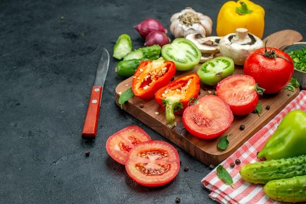 Вид снизу овощи зеленые и красные помидоры болгарский перец на разделочной доске зелень в миске нож огурцы на красной скатерти на черном столе