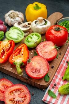 Вид снизу овощи зеленые и красные помидоры желтый болгарский перец на разделочной доске зелень в миске нож огурцы на красной скатерти на черном столе