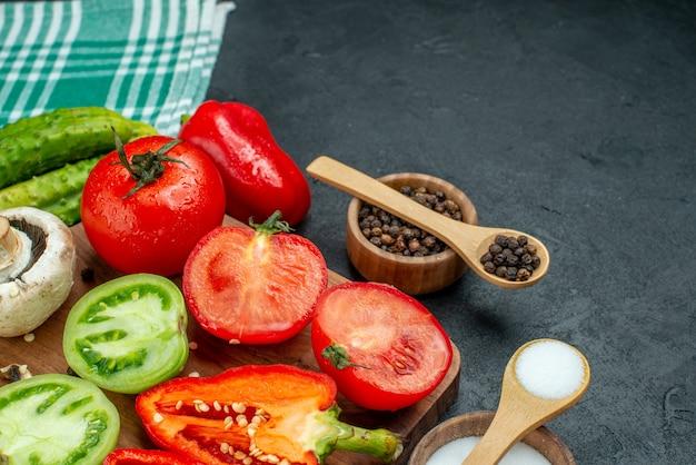 Вид снизу овощи грибы нарезанные помидоры болгарский перец на разделочной доске чеснок черный перец соль в мисках деревянные ложки огурцы на черном столе свободное место