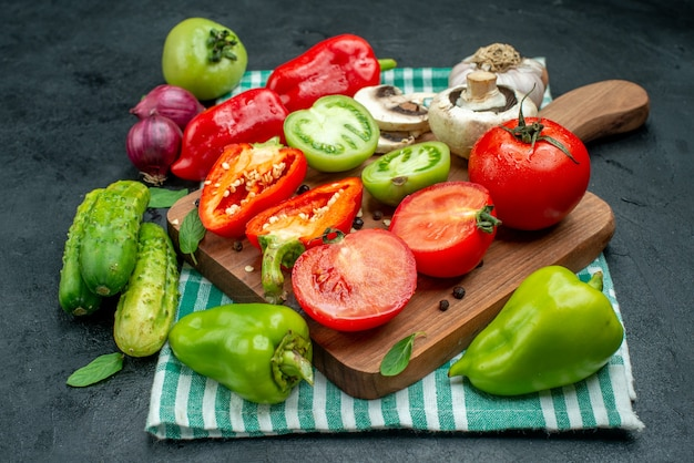 Vista dal basso verdure funghi pomodori peperoni su tagliere aglio cetrioli cipolla rossa su tavola nera
