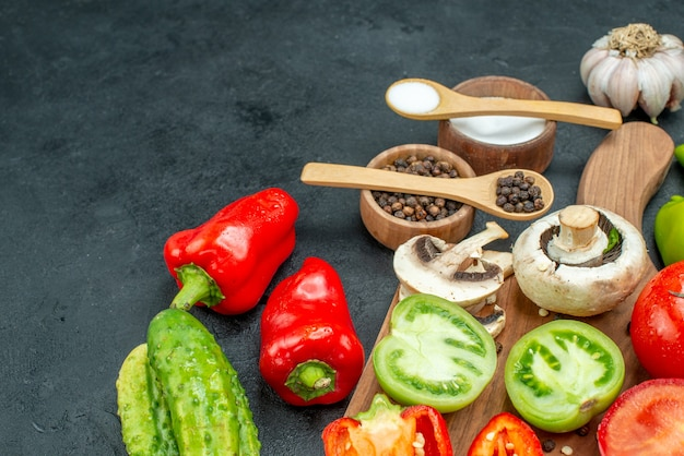 Вид снизу овощи грибы помидоры красный перец на разделочной доске чеснок черный перец и соль в мисках деревянные ложки огурцы на темном столе свободное место