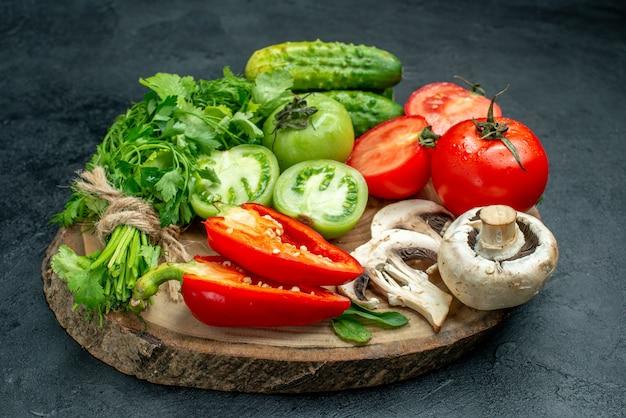 Vista dal basso verdure pomodori peperoni cetrioli verdi funghi su tavola di legno su tavola nera