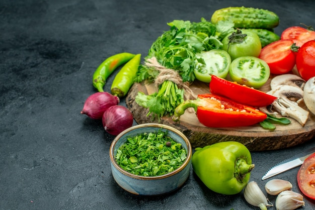 Bottom view vegetables tomatoes bell peppers cucumber greens mushroom on wood board knife bowl with greens onions on black ground