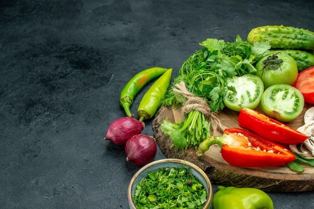 Вид снизу овощи помидоры болгарский перец огурцы зелень на деревянной доске миска с зеленью лук на черном столе свободное пространство