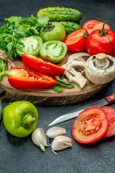 Вид снизу овощи помидоры болгарский перец огурцы зелень на деревянной доске нож на черном столе