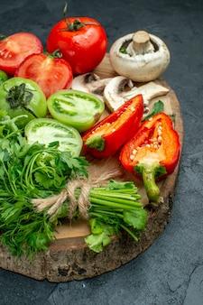 Vista dal basso verdure pomodori peperoni verdi funghi su tavola di legno su tavola scura