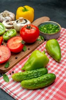 Вид снизу овощи помидоры болгарский перец на разделочной доске зелень в миске огурцы на красной скатерти на черном столе