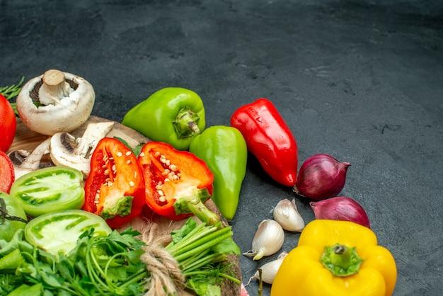 Vista dal basso verdure pomodori peperoni rossi verdi funghi su tavola rustica peperoni piccanti cipolla rossa aglio su tavolo nero spazio libero