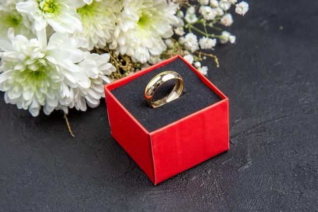 Вид снизу белые цветы обручальное кольцо в коробке на темном фоне