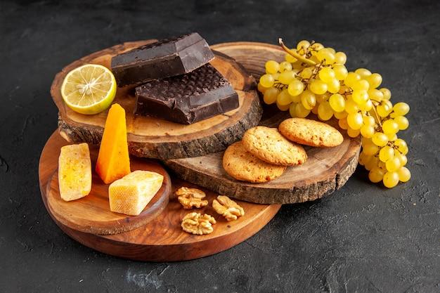 底面図木の板チーズダークチョコレートビスケットブドウの一部が暗いテーブルにレモンをカット