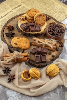 ローストコーヒー豆チョコレートシナモンスティックとテーブルの上のビスケットボウルと木の板の底面図
