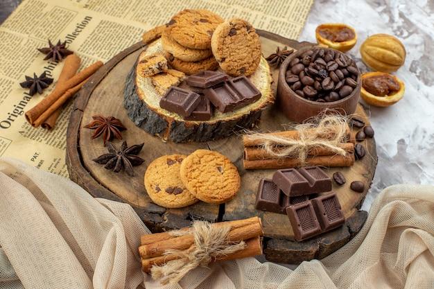 底面図木製の素朴なボードとローストコーヒー豆チョコレートシナモンスティックがテーブルにあるクッキーボウル