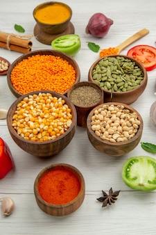 Вид снизу деревянные миски с кукурузными семечками, фасолью, тыквенными семечками, чечевицы, миска с черным перцем, корица, анис на столе