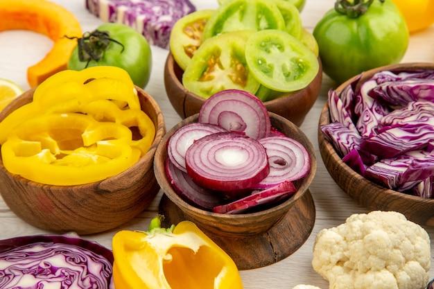 Вид снизу деревянные миски с нарезанными овощами, цветная капуста, лук, красная капуста, зеленый помидор на белой поверхности