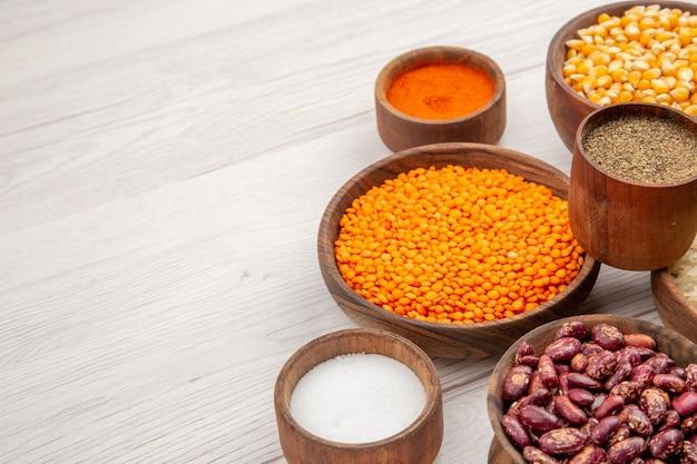 Vista dal basso ciotole di legno con lenticchie semi di mais semi di zucca fagioli spezie diverse sul tavolo grigio spazio libero