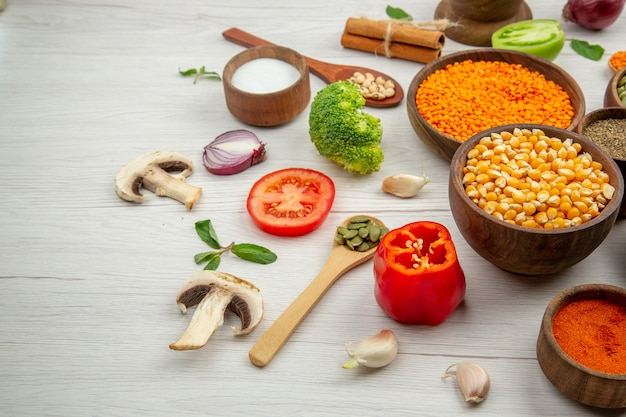 Bottom view wooden bowls with pumpkin seeds lentiles black and red pepper bowls wooden spoons broccoli cinnamons on wooden table