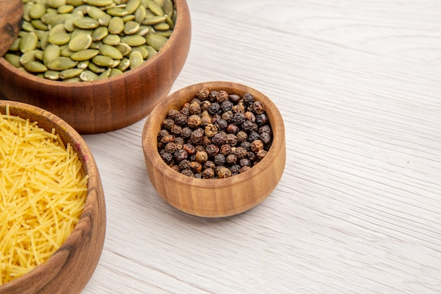 Bottom view wooden bowls with thin pasta tube black pepper pumpkin seeds on grey table free space