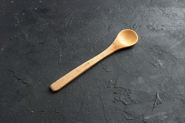 Cucchiaio di legno vista dal basso sul tavolo scuro con spazio libero