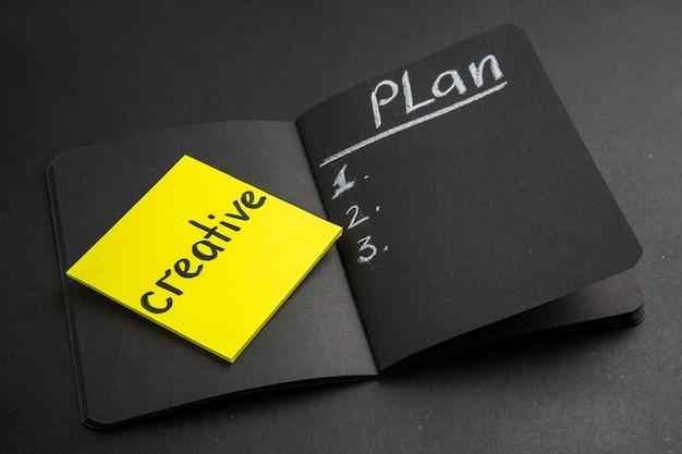 Bottom view word creative written on sticky note plan written on black notepad on black background