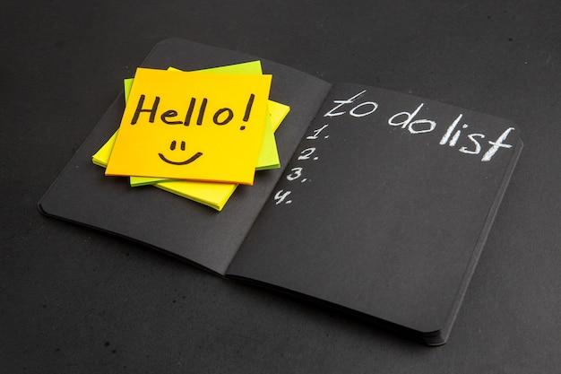 Vista dal basso parola ciao scritta su note adesive per fare la lista sul blocco note nero sul tavolo nero