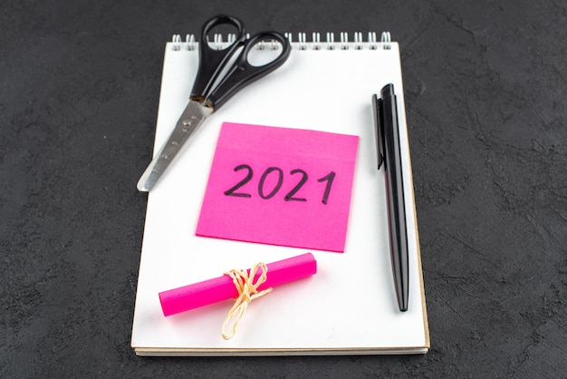Vista dal basso scritta su una nota adesiva rosa forbici penna nera su sfondo scuro